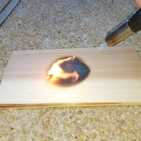 Ignite cedar plank. Use kitchen torch, or the propane sort from a hardware store. Make sure it flames -- no fire, no smoke.